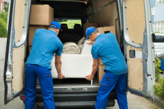 Two Workers Adjusting Sofa In Truck
